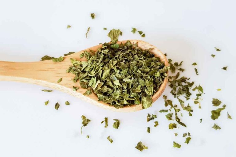 dried parsley in a wooden spoon