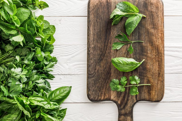 Basil and some other herbs that can be basil substitutes on a wooden board.