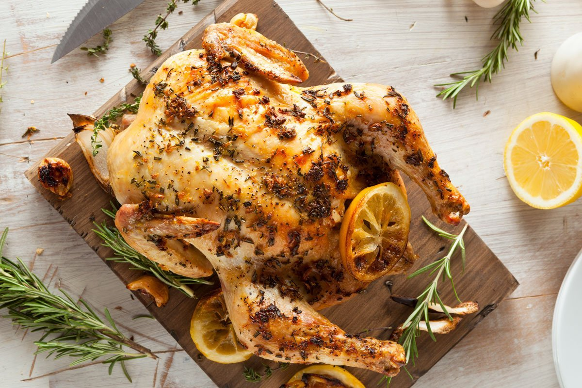 Roast chicken with fresh rosemary and lemon slices.