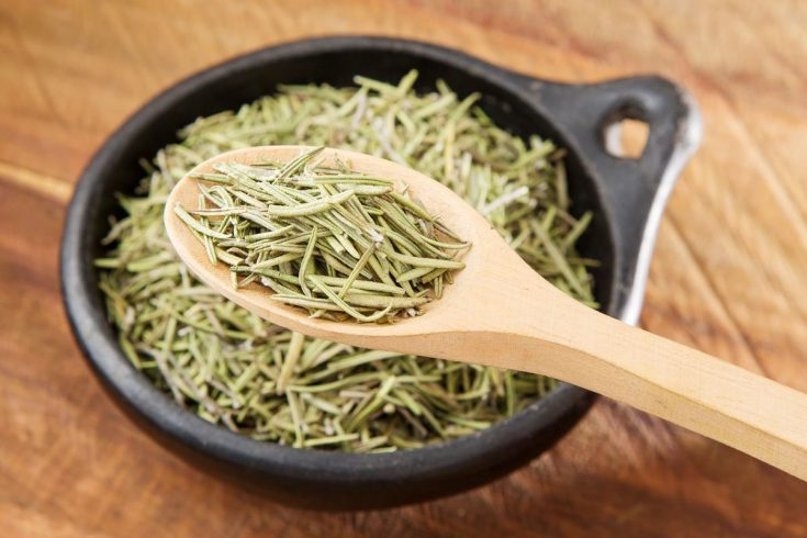 Dried rosemary on a wooden spoon.